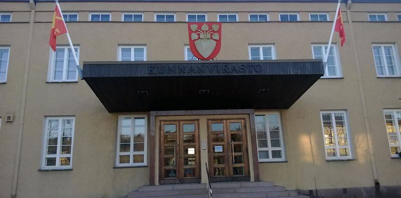 Osuuskunta Pro Perniön tunnusliput liehuvat entisen Perniön vaakunan sivuilla sisäänkäynnin yläpuolella.